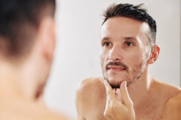 鏡で顔を見る男性