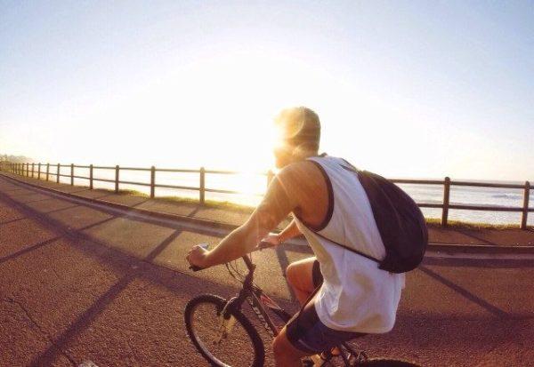 日差し浴びて自転車を漕ぐ男性