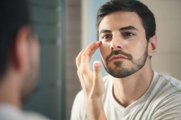 クリームを顔に塗る男性